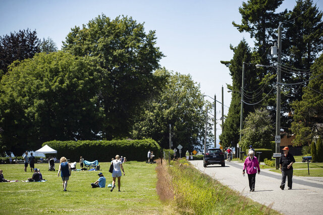 A ditch marks the Canada-U.S. border and separates people walking on the road, right, in Surrey, British Columbia, and those gathered at Peace Arch Historical State Park, left, in Blaine, Wash., Sunday, July 5, 2020. Although the B.C. government closed the Canadian side of the park in June due to concerns about crowding and COVID-19, people are still able to meet in the U.S. park due to a treaty signed in 1814 that allows citizens of Canada and the U.S. to unite in the park without technically crossing any border. (Darryl Dyck/The Canadian Press via AP)
