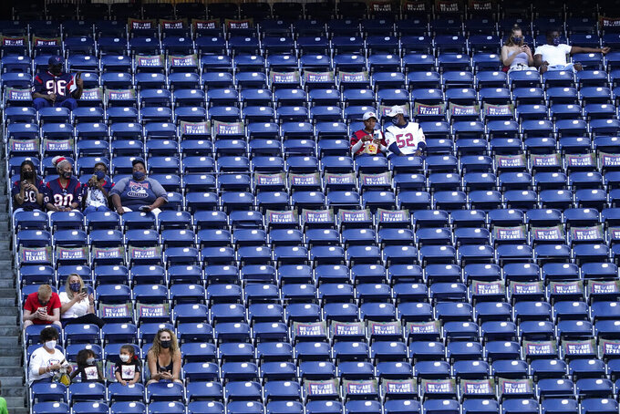 Fans use social distancing as they arrive NRG Stadium for an NFL football game between the Houston Texans and the New England Patriots, Sunday, Nov. 22, 2020, in Houston. (AP Photo/David J. Phillip)