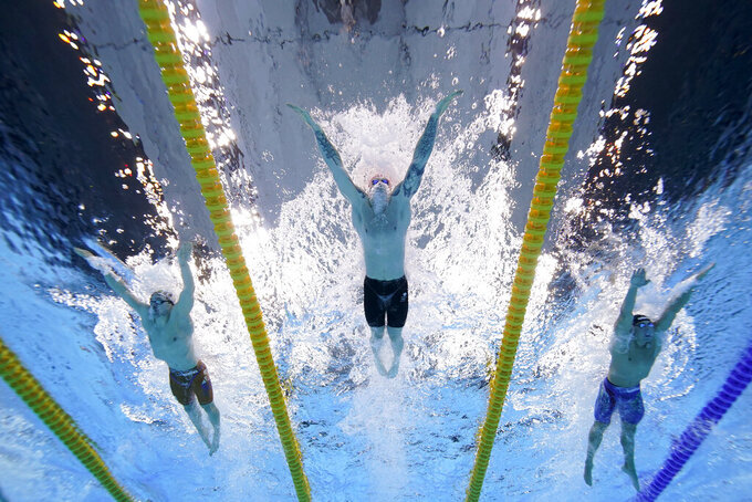 Britain's Adam Peaty, center, swims to win the gold medal in the 100-meter breaststroke final at the 2020 Summer Olympics, Monday, July 26, 2021, in Tokyo. (AP Photo/David J. Phillip)
