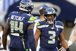 Seattle Seahawks quarterback Russell Wilson (3) greets wide receiver DK Metcalf (14) during warmups before the team's NFL football preseason game against the Los Angeles Chargers, Saturday, Aug. 28, 2021, in Seattle. (AP Photo/John Froschauer)