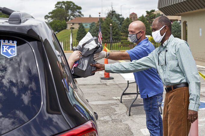 A motorist is handed a bag containing information about open positions at a drive-thru job fair in Omaha, Neb., Wednesday, July 15, 2020. Nebraska reinstated job search requirements this week for most people claiming jobless benefits. Those unemployment insurance requirements were suspended in mid-March to help employees who had lost their jobs due to the coronavirus. (AP Photo/Nati Harnik)