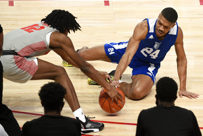 Our Lady of the Lake guard Ethan White (24) and Houston guard Tramon Mark vie for a loose ball during the first half of an NCAA college basketball game, Saturday, Feb. 6, 2021, in Houston. (AP Photo/Eric Christian Smith)