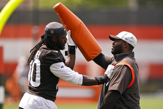 Cleveland Browns linebacker Jadeveon Clowney, left, works with assistant defensive line coach Jeremy Garrett during an NFL football practice, Saturday, July 31, 2021, in Berea, Ohio. (AP Photo/Tony Dejak)