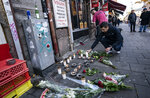 A man lays flowers and a candle outside a restaurant, the scene of a shooting on Saturday, in Malmo, Sweden, Sunday Nov. 10, 2019.  A 15-year-old boy was killed and another teenager was in critical condition after a shooting in a busy square in the southern city of Malmo, Swedish police said Sunday. Similar incidents and explosions in Malmo recently have alarmed politicians and residents. (Johan Nilsson/TT News Agency via AP)