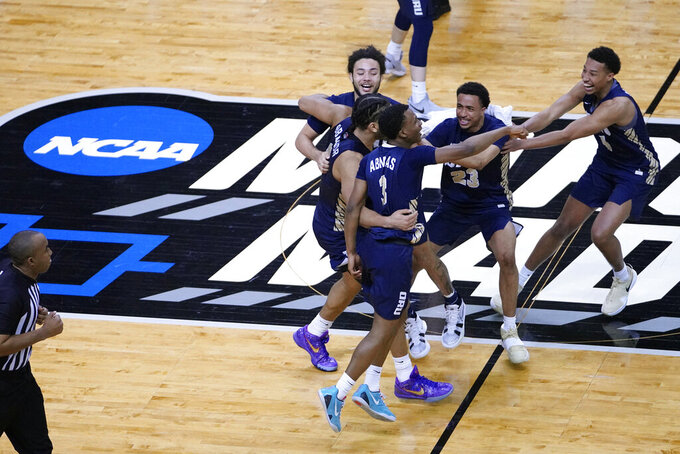 Oral Roberts players celebrate at the end of a college basketball game against Florida in the second round of the NCAA tournament at Indiana Farmers Coliseum, Sunday, March 21, 2021 in Indianapolis. Oral Roberts won 81-78. (AP Photo/AJ Mast)