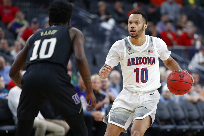 Arizona's Jemarl Baker Jr. drives against Washington's Elijah Hardy during the second half of an NCAA college basketball game in the first round of the Pac-12 men's tournament Wednesday, March 11, 2020, in Las Vegas. (AP Photo/John Locher)