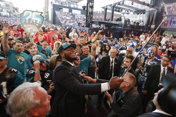 Florida's Jawaan Taylor takes a photo with fans after the Jacksonville Jaguars selected Taylor in the second round of the NFL football draft, Friday, April 26, 2019, in Nashville, Tenn. (AP Photo/Mark Humphrey)