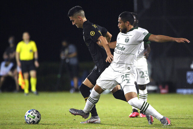 Los Angeles FC midfielder Eduard Atuesta, left, and Portland Timbers defender Bill Tuiloma (25) compete for a ball during the second half of an MLS soccer match, Thursday, July 23, 2020, in Kissimmee, Fla. (AP Photo/Phelan M. Ebenhack)
