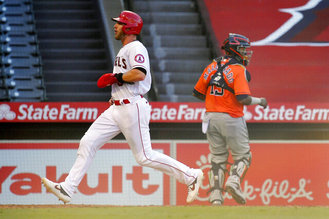 Los Angeles Angels' Taylor Ward, left, scores on a sacrifice fly by David Fletcher as Houston Astros catcher Martin Maldonado stands near the plate during the sixth inning of a baseball game Saturday, Aug. 1, 2020, in Anaheim, Calif. (AP Photo/Mark J. Terrill)