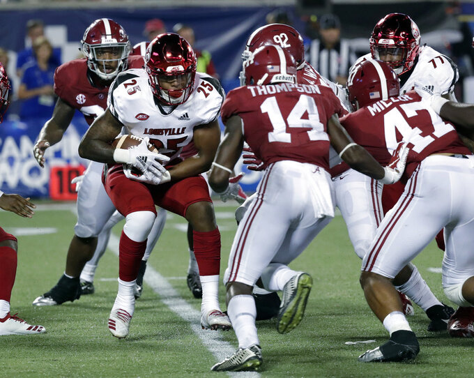 FILE - In this Sept. 1, 2018, file photo, Louisville running back Dae Williams (25) looks for running room against Alabama, including defensive back Deionte Thompson (14), during the second half of an NCAA college football game, in Orlando, Fla. Thompson was named to The Associated Press Midseason All-America team, Tuesday, Oct. 16, 2018.(AP Photo/John Raoux, File)