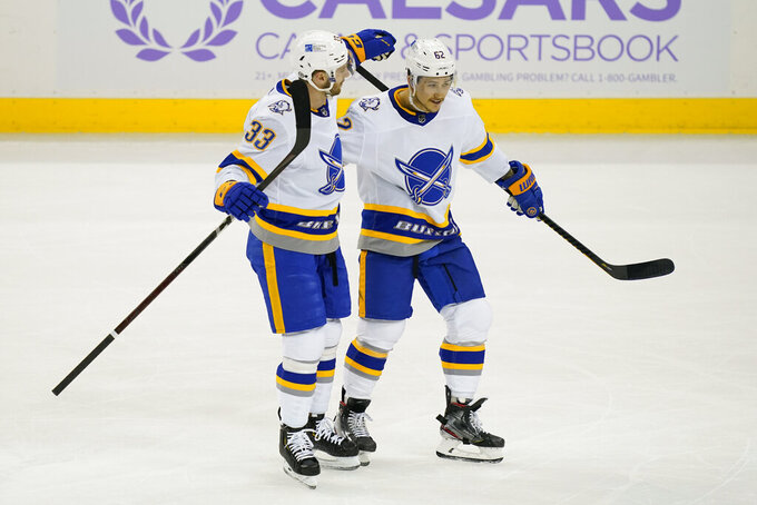 Buffalo Sabres defenseman Brandon Montour (62) celebrates his goal on New Jersey Devils goaltender Scott Wedgewood alongside defenseman Colin Miller (33) during the first period of an NHL hockey game Tuesday, April 6, 2021, in Newark, N.J. (AP Photo/John Minchillo)