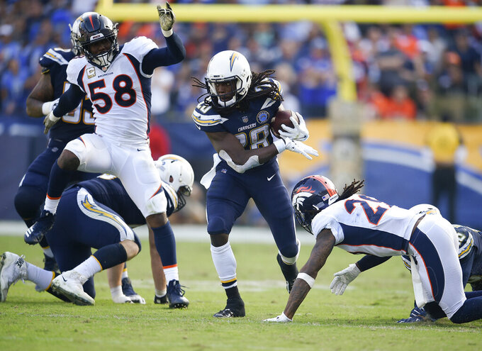 FILE - In this Nov. 18, 2018, file photo, Los Angeles Chargers running back Melvin Gordon runs the ball while Denver Broncos cornerback Bradley Roby, right, defends during the second half of an NFL football game in Carson, Calif. The Chargers are considered one of the AFC's top teams, but they didn't have a smooth summer with Gordon's holdout, and injuries to other players. (AP Photo/Kelvin Kuo, File)