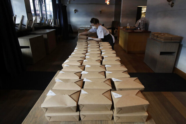 FILE - In this Friday, March 27, 2020, file photo, Nightbird Restaurant pastry chef Hope Waggoner prepares dinner boxes that were to be delivered to hospital workers in San Francisco. California Gov. Gavin Newsom announced Friday, April 24 that taxpayers will pay restaurants to make meals for millions of California's seniors during the coronavirus pandemic, an initiative that could pump billions of dollars into a devastated industry. Nightbird owner Kim Alter said in an email that the restaurant is