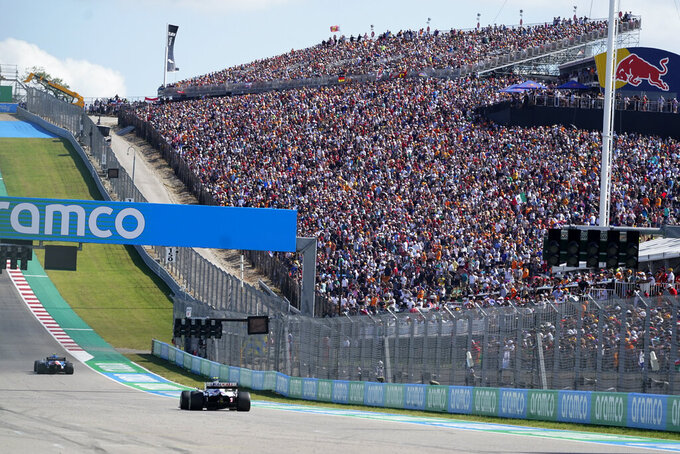 Fans watch as cars approach turn one during the F1 U.S. Grand Prix auto race at Circuit of the Americas, Sunday, Oct. 24, 2021, in Austin, Texas. (AP Photo/Darron Cummings, Pool)