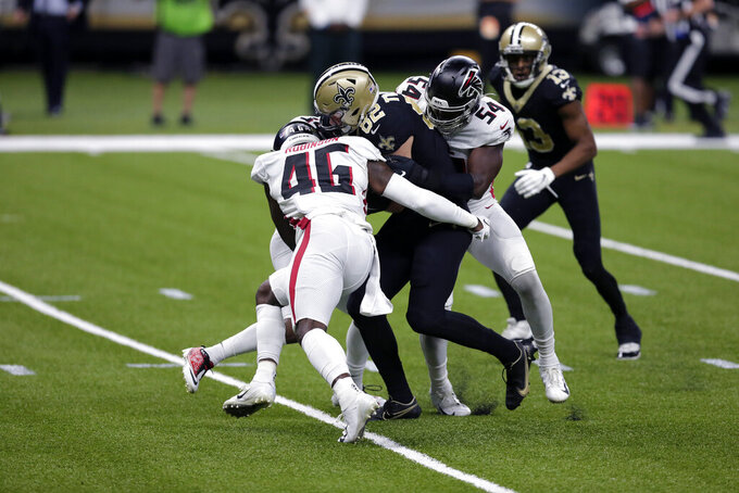 New Orleans Saints tight end Adam Trautman (82) carries on a pass reception as he is tackled by Atlanta Falcons linebacker Edmond Robinson (46) and linebacker Foye Oluokun (54) in the first half of an NFL football game in New Orleans, Sunday, Nov. 22, 2020. (AP Photo/Brett Duke)