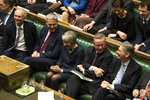 In this handout photo provided by UK Parliament, Britain's Prime Minister Theresa May, centre, laughs during the Brexit debate in the House of Commons, London, Thursday March 14, 2019. Britain's Parliament has voted to seek a delay of the country's departure from the European Union, a move that will likely avert a chaotic withdrawal on the scheduled exit date of March 29.  (UK Parliament/Mark Duffy via AP)