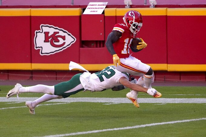 Kansas City Chiefs wide receiver Tyreek Hill (10) fights through the tackle attempt by New York Jets safety Ashtyn Davis (32) after making a catch to score a touchdown in the second half of an NFL football game on Sunday, Nov. 1, 2020, in Kansas City, Mo. (AP Photo/Charlie Riedel)