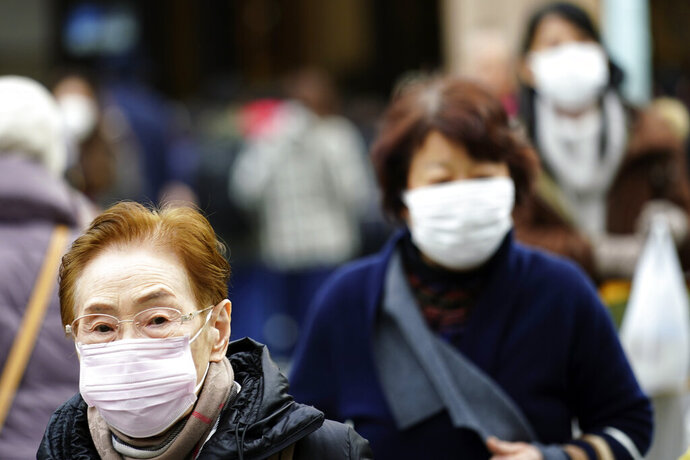 Pedestrians wear protective masks as they walk through a shopping district in Tokyo Thursday, Jan. 16, 2020. Japan's government said Thursday a man treated for pneumonia after returning from China has tested positive for the new coronavirus identified as a possible cause of an outbreak in the Chinese city of Wuhan. (AP Photo/Eugene Hoshiko)