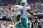 Miami Dolphins running back Salvon Ahmed (26) celebrates his touchdown with Lynn Bowden Jr., right, against the Chicago Bears during the first half of an NFL preseason football game in Chicago, Saturday, Aug. 14, 2021. (AP Photo/David Banks)