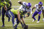 Seattle Seahawks' K.J. Wright, center, picks up the football after a fumble by the Minnesota Vikings as Vikings' Garrett Bradbury (56) moves in during the second half of an NFL football game, Sunday, Oct. 11, 2020, in Seattle. (AP Photo/Ted S. Warren)