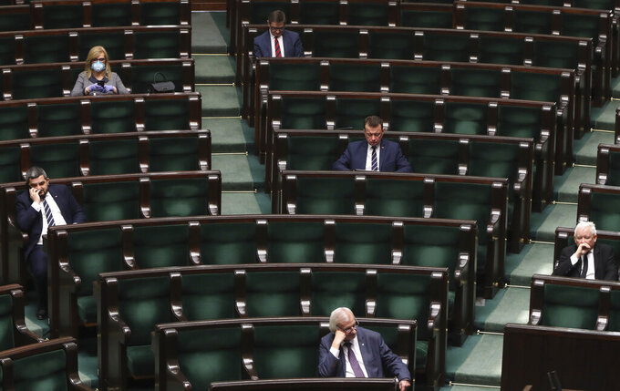 The head of Poland's ruling right-wing Law and Justice party, Jaroslaw Kaczynski, right, and the party's Deputy Parliament Speaker Ryszard Terlecki, center at the bottom, sit at a distance from each other as precaution against the spread of the coronavirus, during an extraordinary session that was to approve new regulations allowing the 460 lawmakers to attend sessions and vote remotely online as precaution against the virus, in Warsaw, Poland, on Thursday, March 26, 2020. (AP Photo/Czarek Sokolowski)