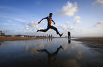 In this photo provided by Reuters, a man jumps over a water stream on a beach along the Arabian Sea in Mumbai, India, on Sept 2, 2013. Danish Siddiqui, a Pulitzer Prize-winning photographer for the Reuters news service was killed Friday, July 18, 2021, as he chronicled fighting between Afghan forces and the Taliban near a strategic border crossing amid the continuing withdrawal of U.S. and NATO troops. (Danish Siddiqui/Reuters via AP)