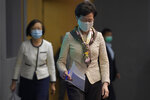 Hong Kong Chief Executive Carrie Lam, right, arrives at a press conference in Hong Kong, Tuesday, June 2, 2020. Lam hit out at the