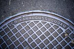 This Thursday, Oct. 31, 2019 photo, shows a manhole cover surviving from communist times in Berlin, when Volkseigene Betriebe, or Publicly Owned Enterprises, manufactured manhole covers for East German streets.(AP Photo/Markus Schreiber)