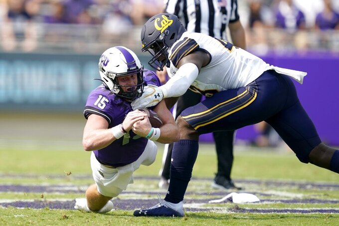 TCU quarterback Max Duggan (15) dives forward for more yardage on a carry as California linebacker Femi Oladejo, right, defends in the first half of an NCAA college football game in Fort Worth, Texas, Saturday, Sept. 11, 2021. (AP Photo/Tony Gutierrez)