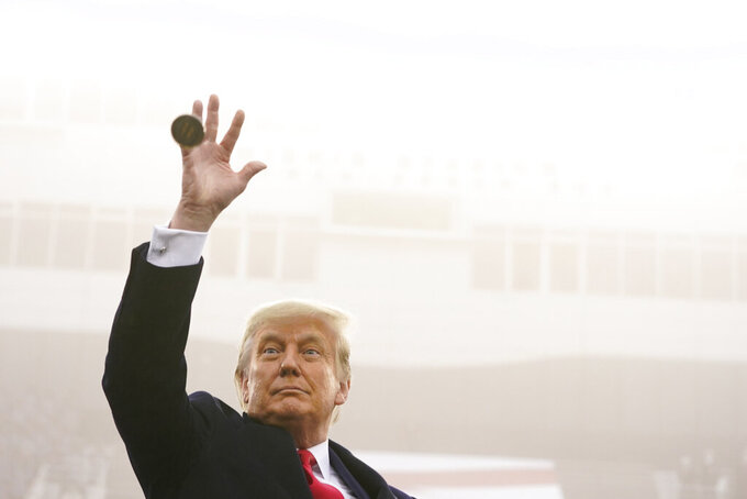 President Donald Trump throws the coin in the air before the start of the 121st Army-Navy Football Game in Michie Stadium at the United States Military Academy, Saturday, Dec. 12, 2020, in West Point, N.Y. (AP Photo/Andrew Harnik)