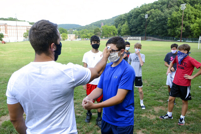 Head coach Zachary Reichert, left, takes Nicholas Giuffre's temperature prior to the start of Pottsville's boys' soccer practice at Alumni Field in Pottsville, Pa., Thursday, Aug. 6, 2020. During a press conference Thursday, Gov. Tom Wolf recommended that no sports take place until January 1, 2021. Previously, state guidelines posted to the Governor's Office website stated that