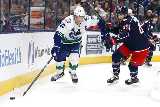 Vancouver Canucks' Bo Horvat, left, and Columbus Blue Jackets' Ryan MacInnis chase a loose puck during the third period of an NHL hockey game Sunday, March 1, 2020, in Columbus, Ohio. The Blue Jackets defeated the Canucks 5-3. (AP Photo/Jay LaPrete)