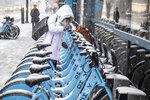 A woman clears off a Divvy bike for a snowy ride at Madison St. and Clinton St. Monday morning, Nov. 11, 2019. (Rich Hein/Chicago Sun-Times via AP)