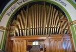 A pipe organ sits inside the sanctuary of the the First United Presbyterian Church, Thursday, July 22, 2021, in Braddock, Pa. Although the original stained glass, pipe organ and chandelier are striking, what is even more interesting about the building is its unique style of architecture. It was built in the Akron-auditorium plan style, with a large sanctuary space separated from smaller Sunday school classrooms by rolling partitions that can be lifted for larger events.  (Pittsburgh Post-Gazette via AP)
