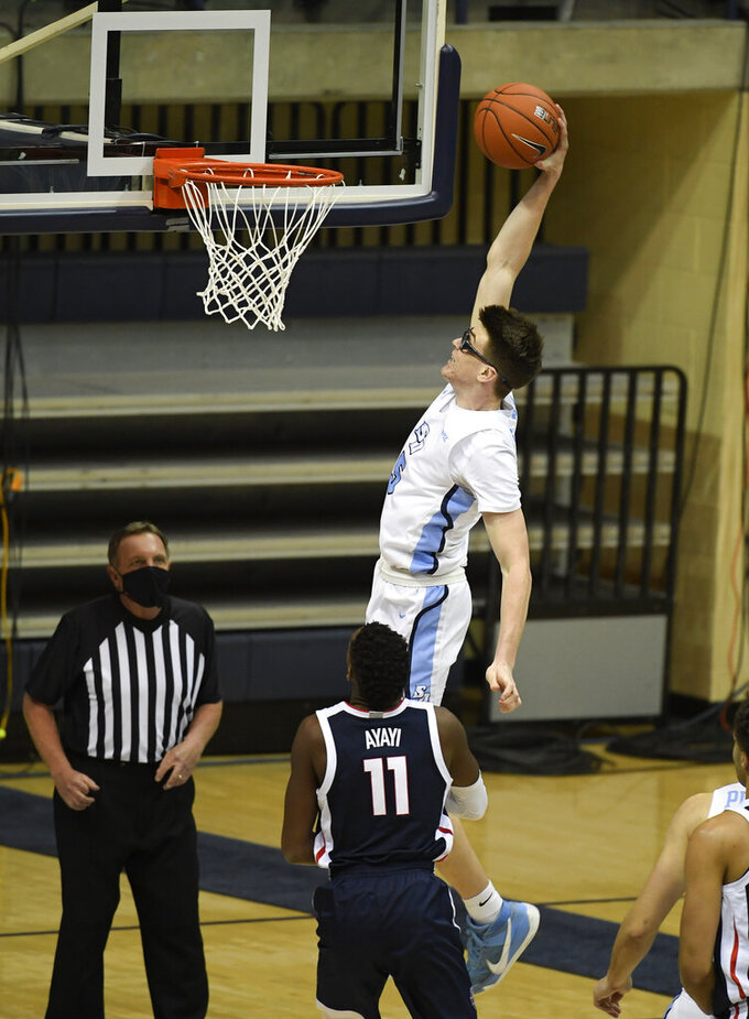 San Diego guard Finn Sullivan (5) dunks over Gonzaga guard Joel Ayayi (11) during the first half of an NCAA college basketball game Thursday, Jan. 28, 2021, in San Diego. (AP Photo/Denis Poroy)
