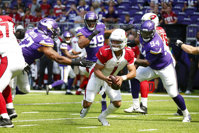Arizona Cardinals quarterback Kyler Murray, center, runs from Minnesota Vikings defenders Everson Griffen, left, and Jaleel Johnson (94) during the first half of an NFL preseason football game, Saturday, Aug. 24, 2019, in Minneapolis. (AP Photo/Bruce Kluckhohn)