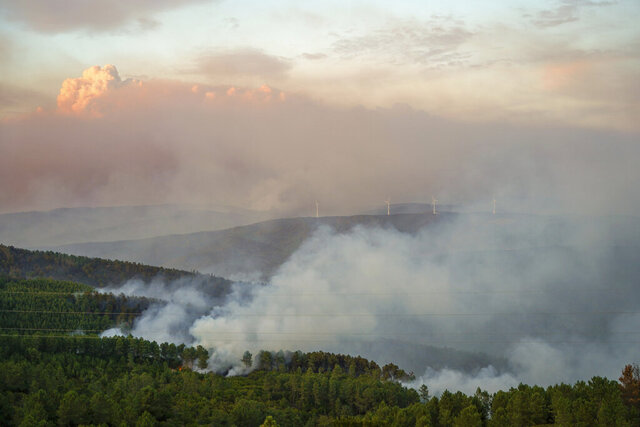 Wind turbines are enveloped in smoke from a fire burning between Proenca-a-Nova and Oleiros, Portugal, Monday, Sept. 14, 2020. Almost 1,000 firefighters and 15 water-dropping aircraft are battling a major wildfire in central Portugal. Officials said that strong winds were pushing the flames through dense and hilly woodland, much of it hard to reach. (AP Photo/Sergio Azenha)