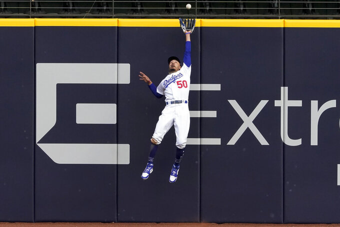 Los Angeles Dodgers right fielder Mookie Betts robs Atlanta Braves' Marcell Ozuna of a home during the fifth inning in Game 6 of a baseball National League Championship Series in Arlington, Texas, on Oct. 17, 2020. (AP Photo/Tony Gutierrez)