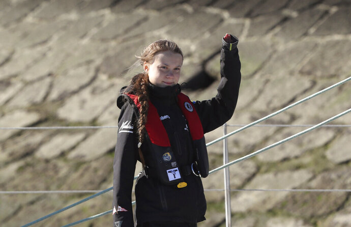 Climate activist Greta Thunberg waves as she arrives in Lisbon aboard the sailboat La Vagabonde Tuesday, Dec 3, 2019. Climate activist Greta Thunberg has arrived by catamaran in the port of Lisbon after a three-week voyage across the Atlantic Ocean from the United States. The Swedish teen sailed to the Portuguese capital before heading to neighboring Spain to attend the U.N. Climate Change Conference taking place in Madrid. (AP Photo/Pedro Rocha)
