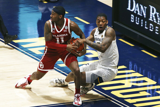 Oklahoma guard De'Vion Harmon (11) and West Virginia forward Gabe Osabuohien (3) tussle for the ball during overtime in an NCAA college basketball game Saturday, Feb. 13, 2021, in Morgantown, W.Va. (AP Photo/Kathleen Batten)