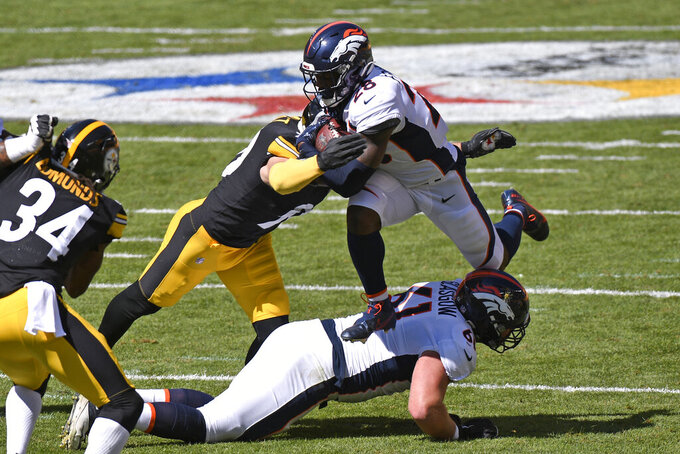 Denver Broncos running back Royce Freeman (28) is tackled by Pittsburgh Steelers outside linebacker T.J. Watt (90) during the first half of NFL football game in Pittsburgh, Sunday, Sept. 20, 2020. (AP Photo/Don Wright)