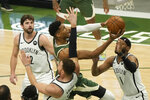 Milwaukee Bucks' Giannis Antetokounmpo shoots past Brooklyn Nets' Bruce Brown and Blake Griffin during the first half of Game 3 of the NBA Eastern Conference basketball semifinals game Thursday, June 10, 2021, in Milwaukee. (AP Photo/Morry Gash)