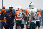 Miami defensive backs coach Travaris Robinson, left, works with safety Bubba Bolden, right, during NCAA college football practice Tuesday, Aug. 10, 2021, in Coral Gables, Fla. (AP Photo/Lynne Sladky)