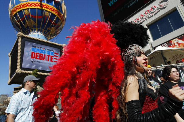 FILE - In this Feb. 19, 2020, file photo, people dressed as showgirls walk near the Paris Las Vegas hotel casino, site of a Democratic presidential debate, in Las Vegas. If Nevada has one job in the Democratic primary, it's to offer something different. And in many ways it has delivered. As the presidential race turned to the state this week, gone was the earnestness of Iowa and tradition of New Hampshire and in its place was racial diversity, a new unpredictability and the muscle of urban, union politics. (AP Photo/John Locher, File)