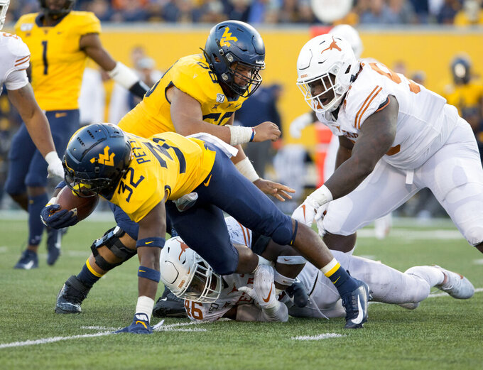 West Virginia running back Martell Pettaway (32) is tackled by Texas linebacker Joseph Ossai (46) during the second half of an NCAA college football game Saturday, Oct. 5, 2019, in Morgantown, W.Va. (AP Photo/Raymond Thompson)