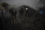 Palestinians work at a traditional charcoal production site in the town of Jabaliya, Northern Gaza Strip, Thursday, Jan. 7, 2021.(AP Photo/Khalil Hamra)