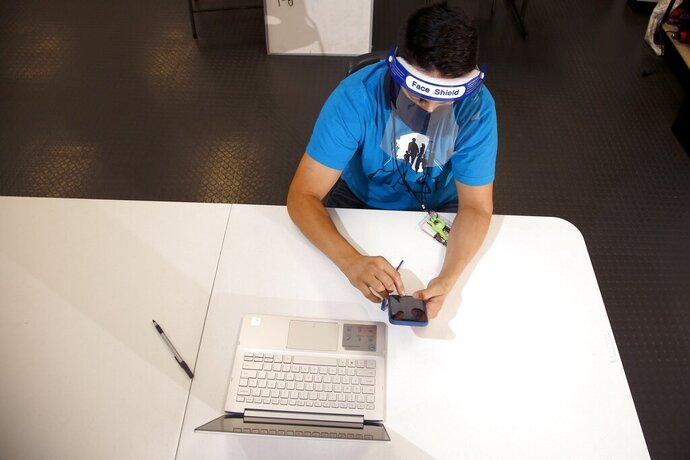 FILE - In this Aug. 6, 2020, file photo wearing a face covering and face shield while working due to the coronavirus, Maico Olivares, lead voter registration organizer for Central Arizonans for a Sustainable Economy, works his phone and computer as he tries to reach about 25 people a day, mostly within the Latino community, to persuade them to register to vote in Phoenix. (AP Photo/Ross D. Franklin, File)