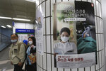 People wearing face masks to help protect against the spread of the coronavirus walk by a poster informing mandatory mask wearing at a subway station in Seoul, South Korea, Sunday, Sept. 20, 2020. South Korea's new coronavirus tally has fallen below 100 for the first time in more than a month. The banner reads:
