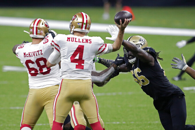 New Orleans Saints outside linebacker Demario Davis (56) pressures San Francisco 49ers quarterback Nick Mullens (4) in the first half of an NFL football game in New Orleans, Sunday, Nov. 15, 2020. (AP Photo/Butch Dill)