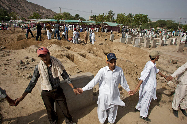 FILE - In this May 29, 2010 file photo, people from a minority Muslim Ahmadi Community stand guard as others preparing to bury the victims of attack by Islamic militants, in Rubwah, some 150 kilometers (93 miles) northwest from Lahore Pakistan. The U.S. Commission on International Religious Freedom on Friday, Jan. 8, 2021, adopted 55-year-old Ramazan Bibi, jailed on blasphemy charges in Pakistan, as a prisoner of conscience. According to a December report by the U.S. Commission for International Religious Freedoms, Pakistan recorded the most cases of blasphemy in the world even though 84 countries have criminal blasphemy laws on their books. (AP Photo/Anjum Naveed, File)